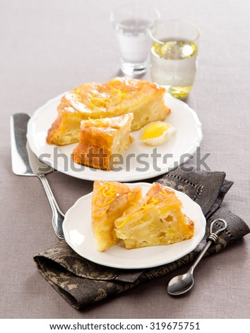 cake with fruit apples pears on a white plate with lemon zest beige linen tablecloth - stock photo