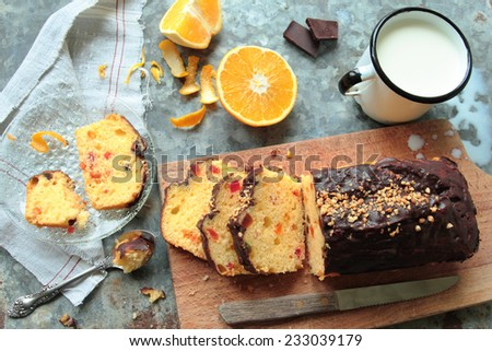 Cake with fruits and chocolate glaze with mug of fresh milk - stock photo