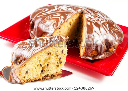 cake with glaze of chocolate in the red dish on the white table - stock photo