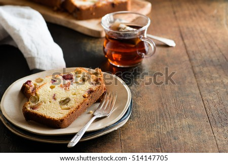 Cake with grapes and plums, sliced on plate over rustic background, selective focus, copy space