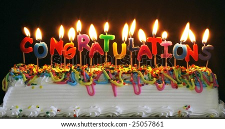 cake with lit candles spelling congratulations