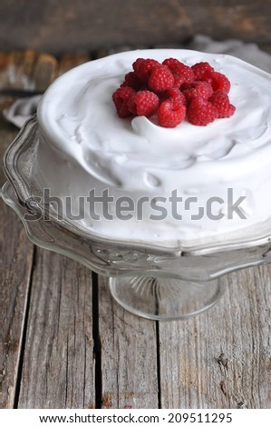 Cake with meringue frosting and raspberries, selective focus