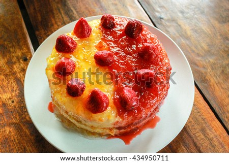 Cake with orange jam and strawberries on a plate.