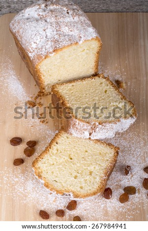 Cake with raisin and sugar powder on the wooden table. Selective focus. - stock photo