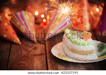 cake with sparkler on table on wooden background - stock photo