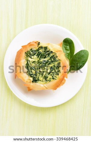 Cake with spinach on white plate, top view