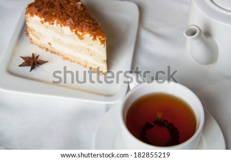 Cake with tea for breakfast surrounded by flowers - stock photo