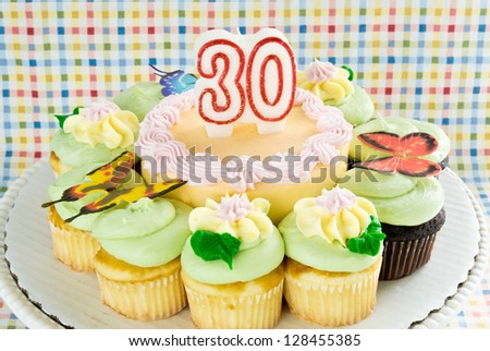 cake with unlit 30 thirty year candle. cake is surrounded by chocolate and yellow cupcakes. Ornate decorations include butterflies and flowers made from butter cream icing. - stock photo