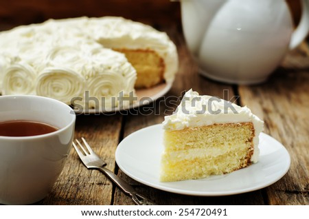 cake with vanilla cream in the form of roses on a dark wood background. tinting. selective focus - stock photo