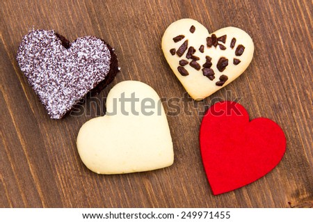 Cakes and cookies in the shape of heart on wooden table seen from above - stock photo