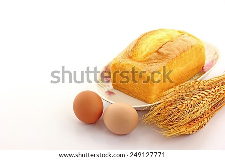 Cakes, eggs, and wheat on white background. - stock photo