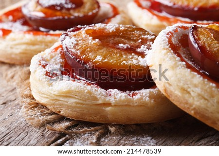 Cakes of puff pastry with plums macro on an old table. horizontal   - stock photo