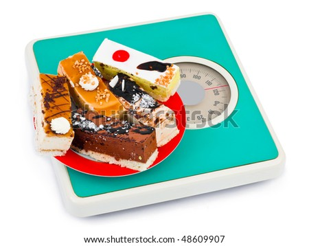 Cakes on weight scale isolated on white background - stock photo