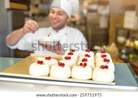 Cakes with confectioner in uniform on the background in the store - stock photo