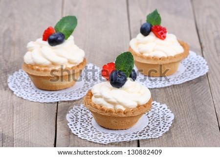 cakes with cream and berries on wooden background - stock photo
