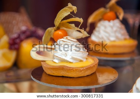 Cakes with meringue and berries of cape gooseberry on a show-window of shop - stock photo
