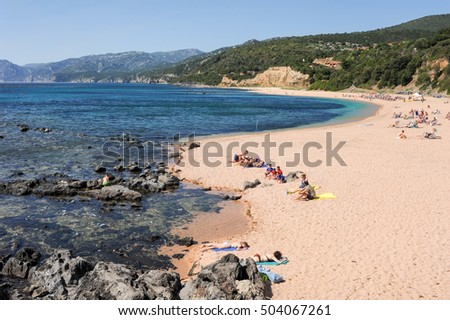 Cala Gonone, Italy - 28 June 2013: people swimming and sunbathing at Cala Gonone beach on Sardinia, Italy