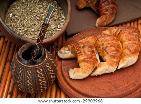Calabash cup for mate and croissants, with yerba mate in the foreground. Mate is a very popular tradition in Argentina and Uruguay. - stock photo