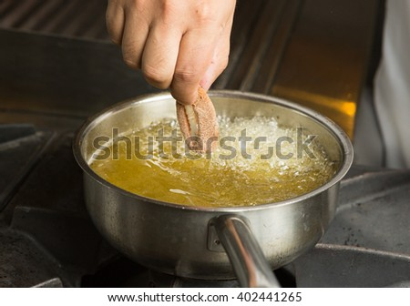Calamari ring being placed into a pan of hot bubbling oil. - stock photo