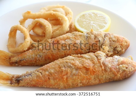 Calamari rings and red mullet  fishes on plate - stock photo