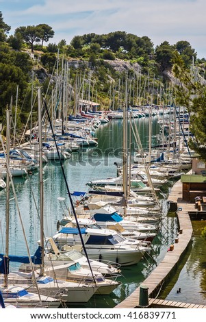 Calanque National Park - small fjords between Marseille and Cassis. White sailboats moored in rows near woody shore. Good weather in May - stock photo
