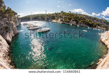 Calanques bay with azure blue water with white sailingboats surrunded by rocks and pine trees