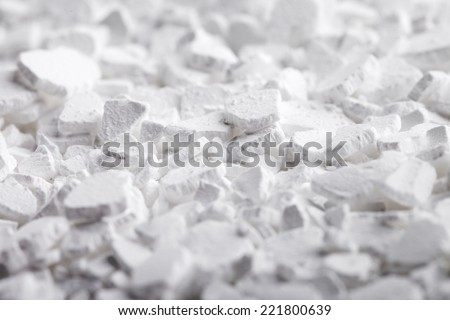 Calcium chloride (CaCl2) flakes. Common applications include brine for refrigeration plants, ice and dust control on roads, and desiccation.  - stock photo