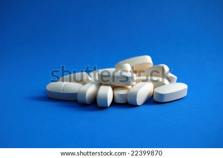 Calcium Pills on Blue Background - stock photo