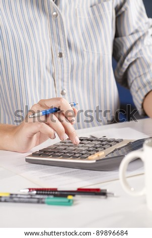 calculate, female model holding pencil using calculator. - stock photo