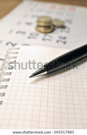 Calculating Expenses concept. Pen, calendar, notebook, and coins