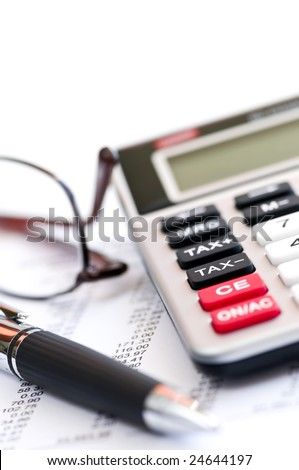 Calculating numbers for income tax return with glasses pen and calculator - stock photo