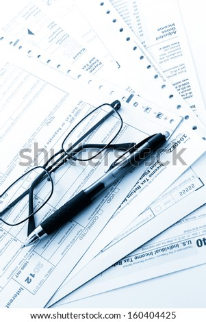 Calculating numbers for income tax return with pen and calculato
