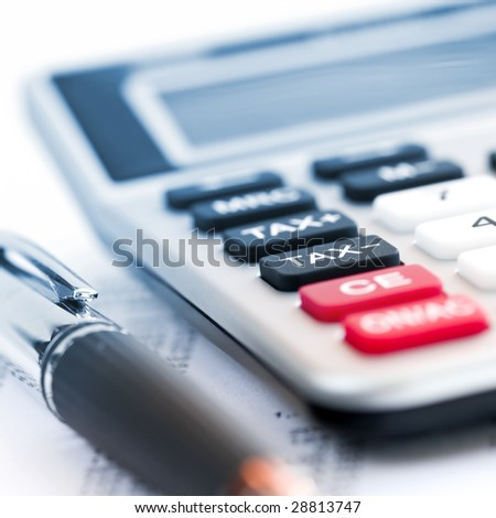 Calculating numbers for income tax return with pen and calculator - stock photo