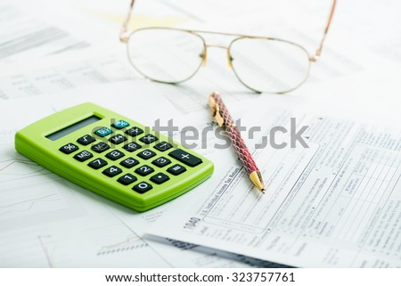 Calculating numbers for income tax return with pen, glasses and calculator - stock photo