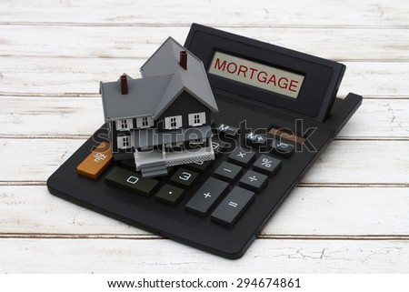 Calculating your mortgage payments, A gray model house on a calculator with word Mortgage over a distressed wood background - stock photo