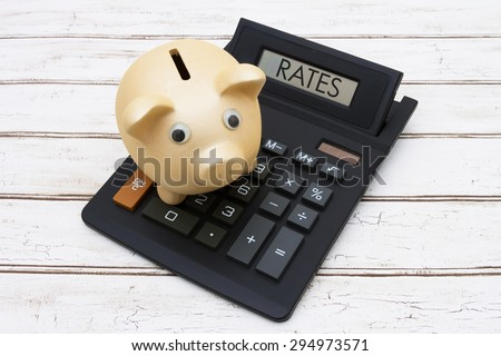 Calculating your rates, A golden piggy bank on a calculator with word Rates over a distressed wood background - stock photo