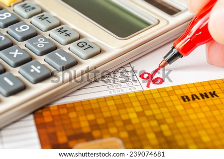 Calculation of interest on a loan calculator and bank cards on table - stock photo