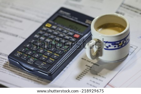 Calculation of the utility bills. Scene with bills, calculator and coffee  - stock photo