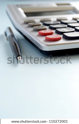 calculator and a pen on a blue background
