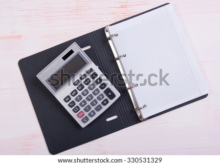 Calculator and blank notepad with copy space - stock photo