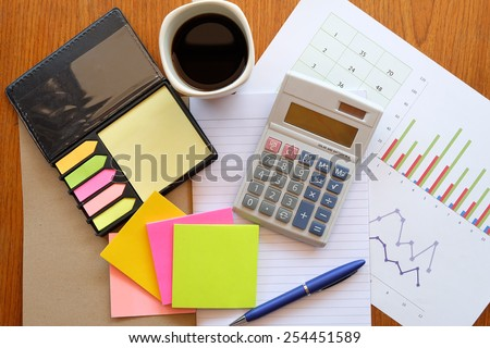 calculator and chart on the wooden table with back coffee    - stock photo