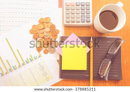 calculator and chart on the wooden table with vintage color concept - stock photo
