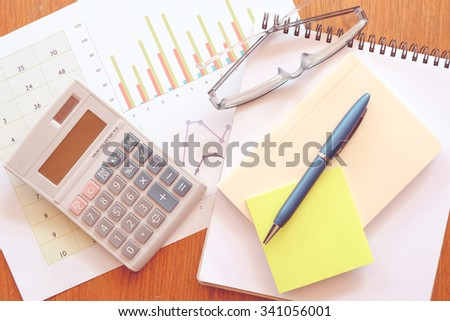 calculator and chart on the wooden table with vintage color style