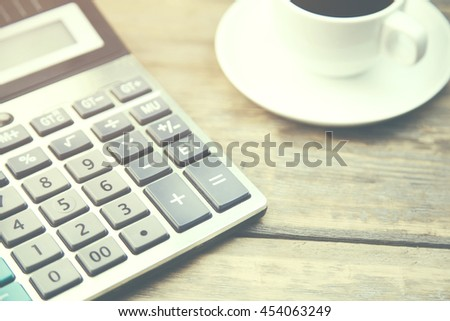 calculator and coffee on wooden table - stock photo