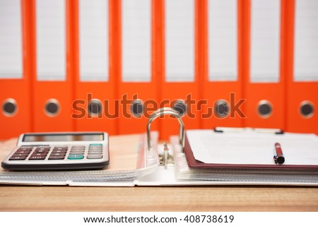 calculator and document on top  of open folder with documentation in background, accounting concept - stock photo