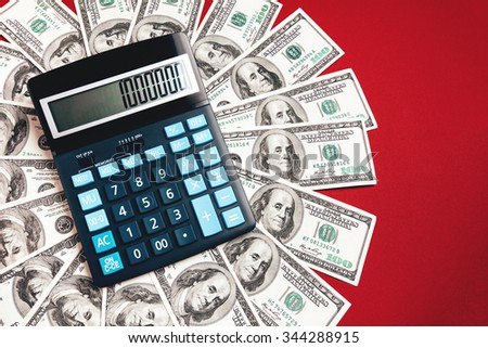 Calculator and dollars in one nundred banknotes, closeup - stock photo