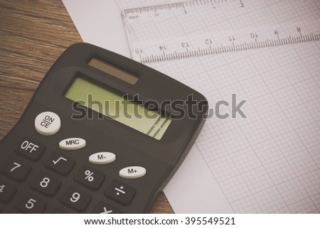 Calculator and drawing equipment and graph paper on a table