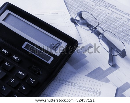 Calculator and glasses on financial documents. Toned blue. Shallow DOF.