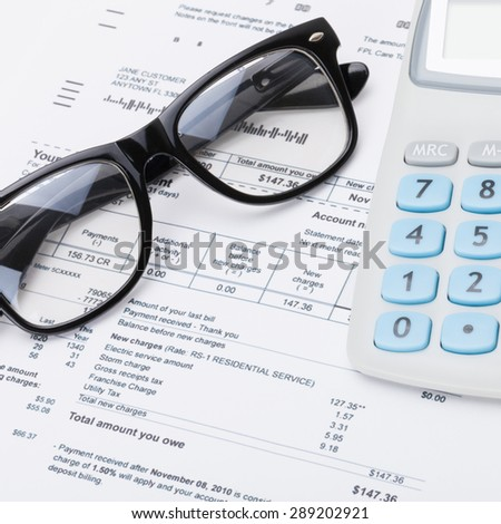 Calculator and glasses with utility bill under it - close up studio shot - stock photo