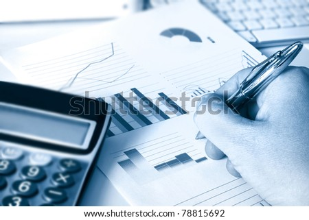 calculator and graphs representing a business financial performance - stock photo
